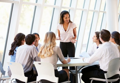 businesspeople-gathered-around-table-woman-standing-and-speaking_web