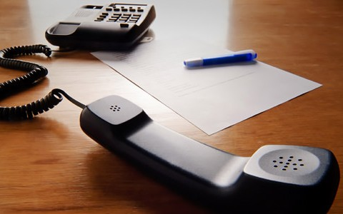 A landline office phone is shown sitting on a table next to a paper and pen with the receiver off the hook.